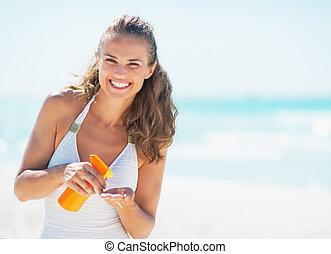 retrato, de, sorrindo, mulher jovem, com, bloco sol, creme