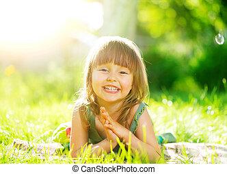 retrato, de, um, menina pequena sorrindo, mentindo, ligado, grama verde
