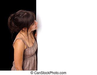 retrato, de, um, mulher jovem, peeking, atrás de, vazio, parede