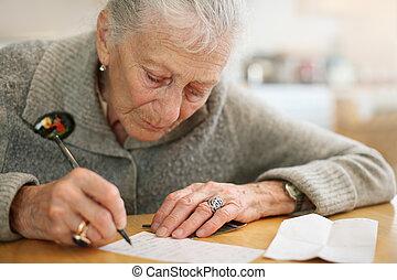 retrato, de, um, sênior, senhora, writing., close-up, raso, dof.