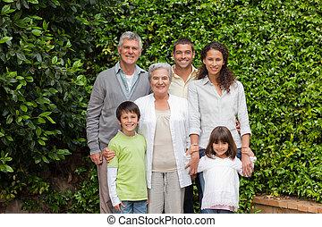 retrato, de, un, familia feliz, mirar la cámara, en el jardín
