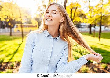 retrato, de, un, hermoso, niña sonriente, en, un, camisa azul, pelo volar, en, el, otoño, en el parque