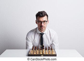 retrato, de, un, joven, en, un, estudio, el sentarse en la tabla, con, tablero del ajedrez, game.