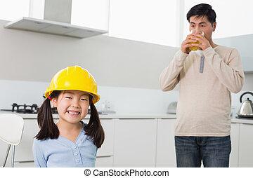retrato, de, un, lindo, niña, en, sombrero duro amarillo, con, padre, bebida, jugo de naranja, en la cocina, en casa