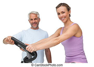 retrato, de, un, mujer feliz, en, bici inmóvil, con, entrenador