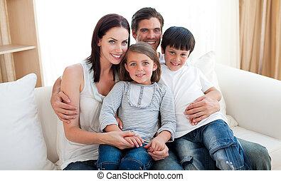 retrato, de, un, sonriente, familia , se sentar sobre el sofá