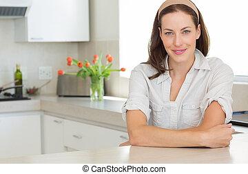 retrato, mulher sorridente, jovem, cozinha