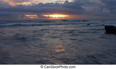 Retreating view of waves on the ocean during sunset. Sea waves on a rocky shore in beautiful warm evening light