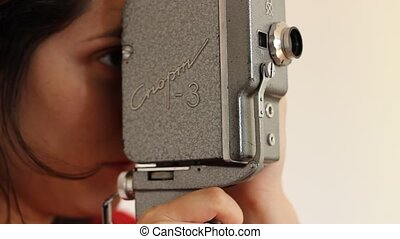 Retro 8mm Film Camera - Lateral view of girl filming on 8 mm...