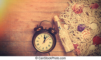 Retro alarm clock and net with shells and bottle on wooden...