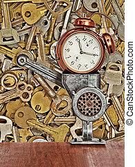 Retro alarm clock in meat grinder on old metal keys background.
