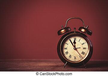 Retro alarm clock on a table. Photo in retro color image ...