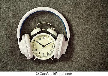Retro alarm clock with white headphones on gray knitting