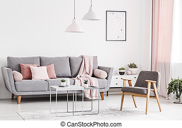 Retro armchair, grey sofa with pink pillows and coffee tables in an elegant living room interior. Real photo