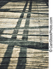 Shadows on a wooden board bridge