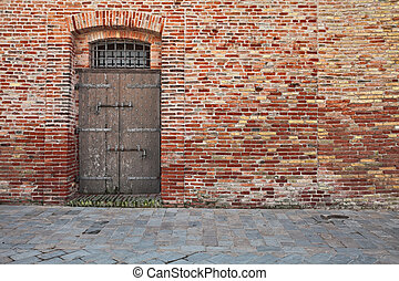 old brick wall, stone paved sidewalk and ancient wooden door
