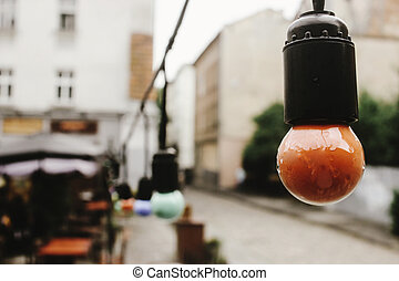 retro beautiful lamp lights on garland at cafe terrace in the street in europe city holiday, space for text