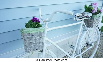 Retro Bicycle with two baskets of flowers on the background of a blue house shot from front to back