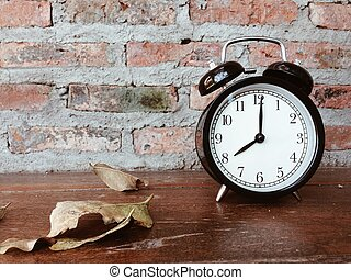 Retro black alarm clock and dry leaves on wooden table