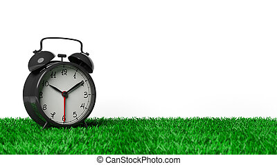 Retro black alarm clock on grass, isolated on white background.