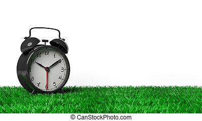 Retro black alarm clock on grass, isolated on white background.