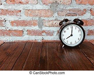 Retro black alarm clock on wooden table