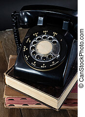 retro black telephone on books