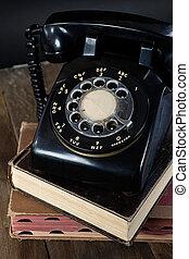 retro black telephone on books