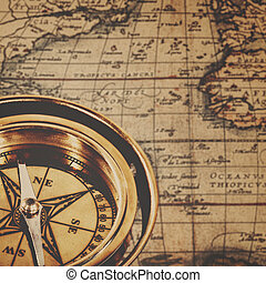 Retro brass compass over antique paper map, adventure backgrounds