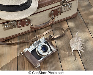 retro camera and hat on wooden background with suitcase and sea shell