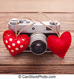 Retro Camera with red hearts on wooden background. - Retro...