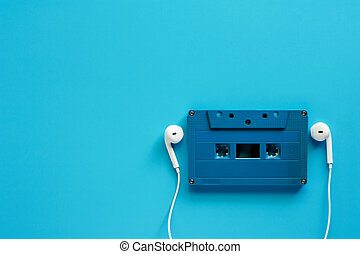 Retro cassette tape with earphones on blue background