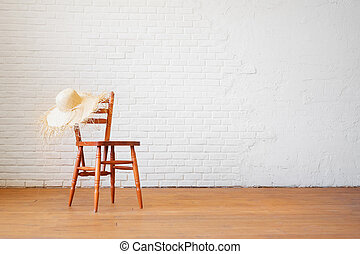 Retro chair with a straw hat on the background of an empty brick white wall in the interior in the loft style. Realistic blank for interior design. Travel delayed during the coronavirus epidemic.
