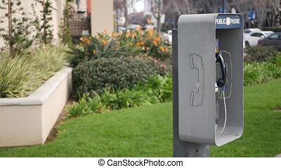 Retro coin-operated payphone station for emergency call on street, California USA. Public analog pay phone booth. Outdated technology for connection and telecommunication service. Cell handset on box.