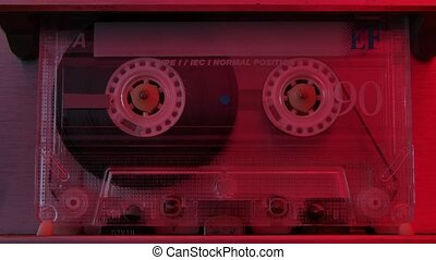Retro compact audio cassette playing extreme close up. Vintage music cassette playing back in the player illuminated by red neon lights. Slow motion