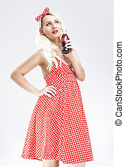 Retro Concepts. Sexy Caucasian Pinup Blond Woman With Drink Bottle Posing in Polka Dotted Dress