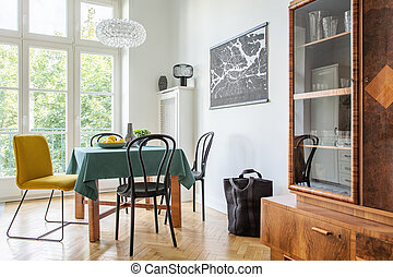 Retro dining room interior with a table, chairs and cupboard in a tenement house