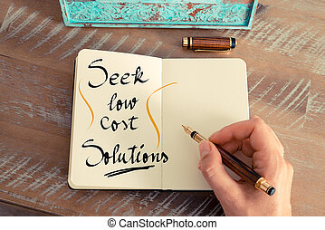 Retro effect and toned image of a woman hand writing a note with a fountain pen on a notebook. Handwritten text Seek Low Cost Solutions as business concept image