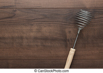 retro egg whisk with wooden handle on brown table with copy...