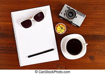 Retro film photo camera, sunglasses, cupcake, cup of coffee and notebook with pencil on brown table. Top view.