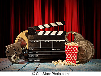 Retro film production accessories placed on wooden planks. Concept of film-making. Red curtain on background