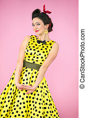 Retro girl. Beautiful woman in a dress with polka dots on a bright background.