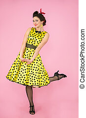 Retro girl. Beautiful woman in a dress with polka dots on heels on a bright background.