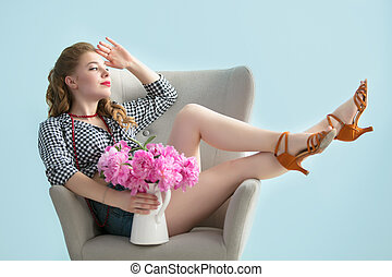 Retro girl in a chair with a bouquet of flowers.