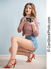 Retro girl in heels with a retro camera.
