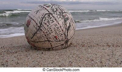 Retro globe on the sand by sea