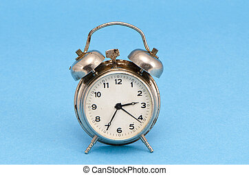 Retro grunge rusty alarm clock blue background