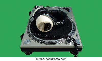Retro headphones spinning on a record player