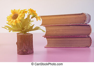 Retro home decor: a stack of books, flowers  on a white wall shelf