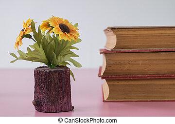 Retro home decor: a stack of books, flowers  on a white wall shelf